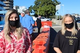 Two women wearing face masks stand either side of barricade with blue sky behind them