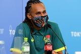Wearing a mask with Indigenous art printed on it, Patty Mills sits in front of a microphone