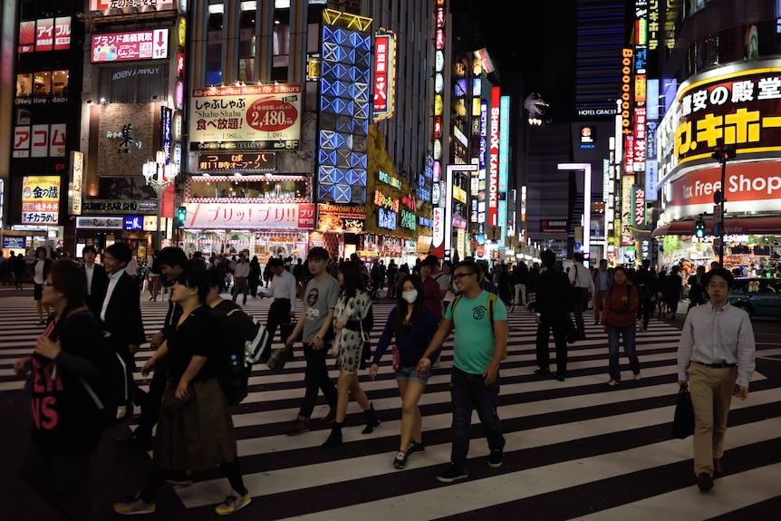 People cross a major intersection in Tokyo at night.