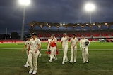 The floodlights shine on the field as clouds loom over the Australian players