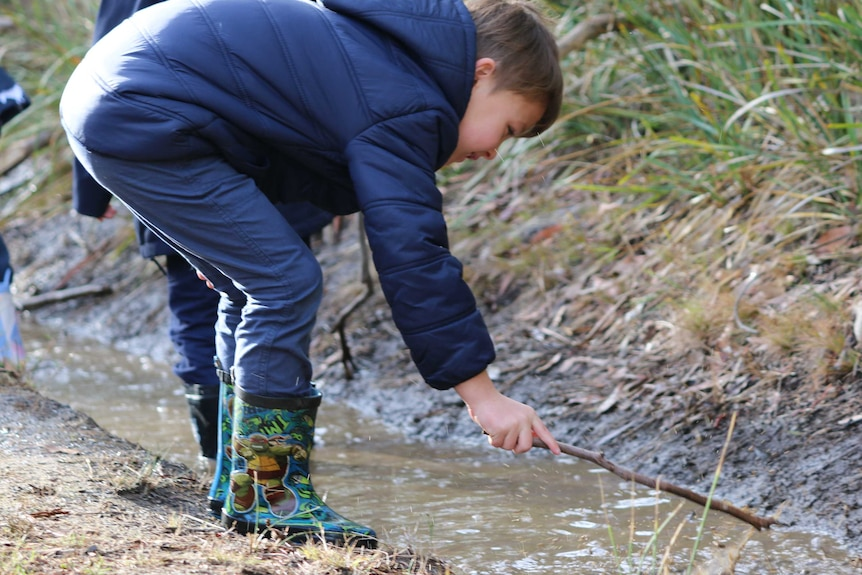 A child in gumboots and jacket pokes a stick at some water