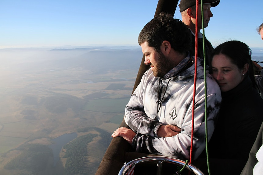Two people look out from a hot air balloon over Tasmania.