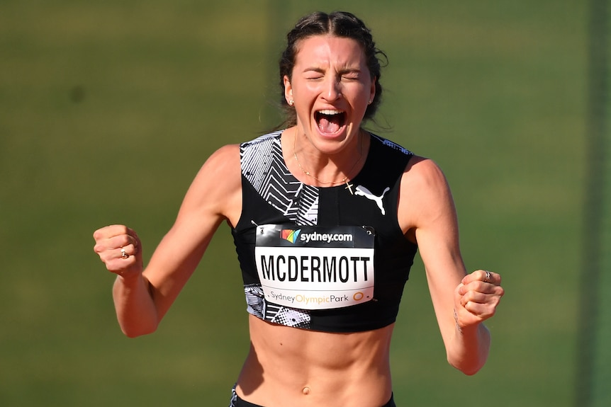 A female high jumper pumps her fists and screams in delight after setting a national record.