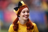 Woman wearing a red wig and yellow shirt smiles.