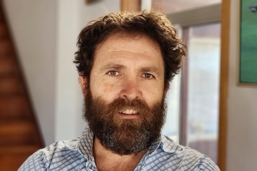 A man with a beard wears a check shirt.