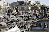 Civil defence workers and people search for survivors under the rubble of houses destroyed by an air strike