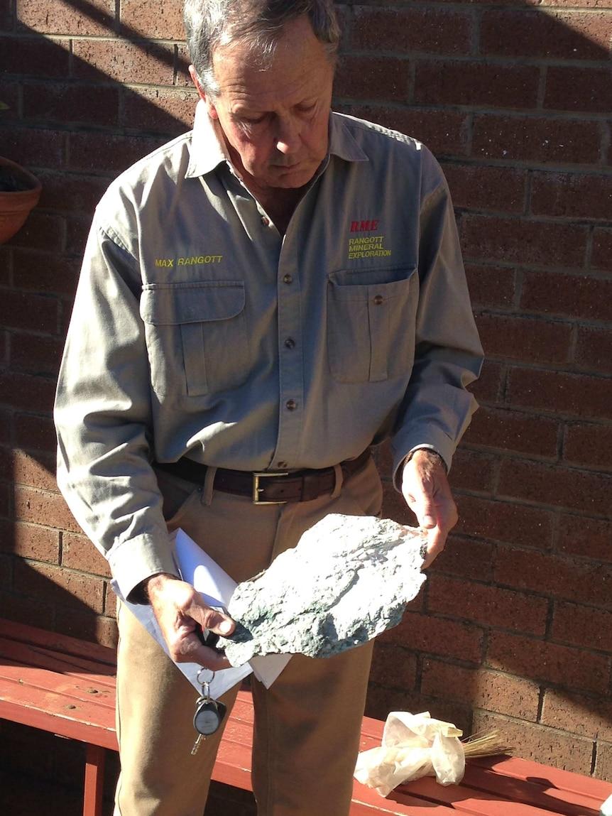 Geologost Max Rangott holding a piece of rock containing asbestos.