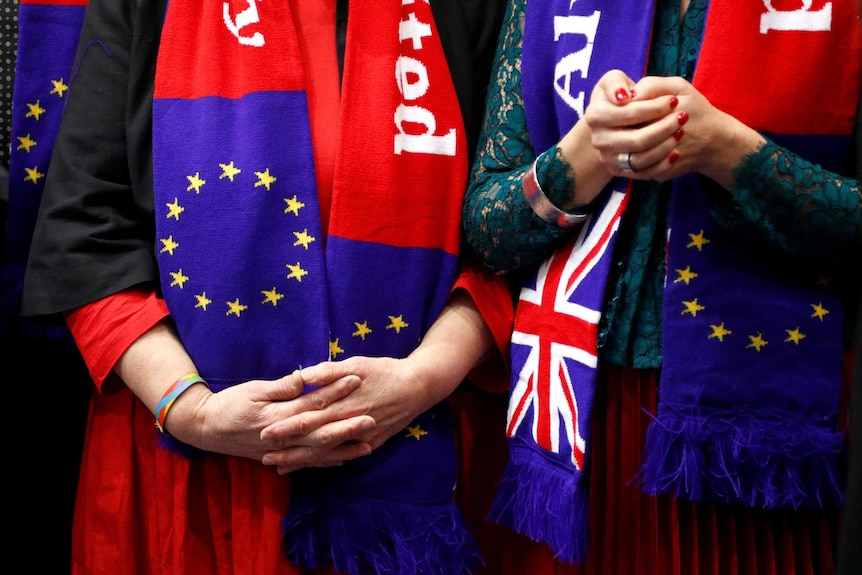 Close up of two women, hands clasped, wearing EU and UK flag scarves