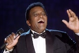 Charley Pride performs in a suit during his induction into the Country Music Hall of Fame