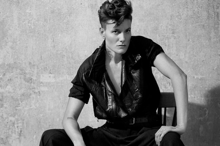 A black and white photo of female model Casey Legler posing while sitting on a stool.