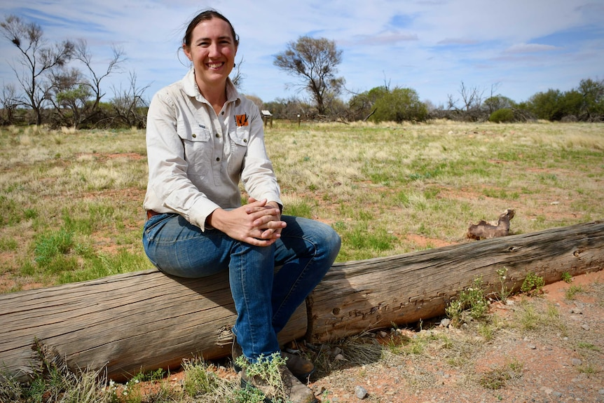 A woman with a brown ponytail, wearing blue jeans and a grey shirt, sits smiling on a log on a grassy plain.