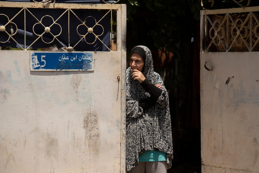A woman in a head scarf peers out her doorway