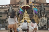 Three people kneel on the ground in front of a gold statue.