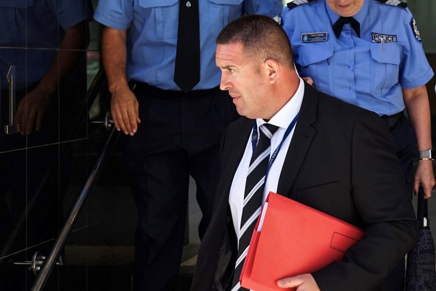 Sergeant Matthew Edmunds outside a Perth court, with a red folder tucked under his arm and two police officers behind him.