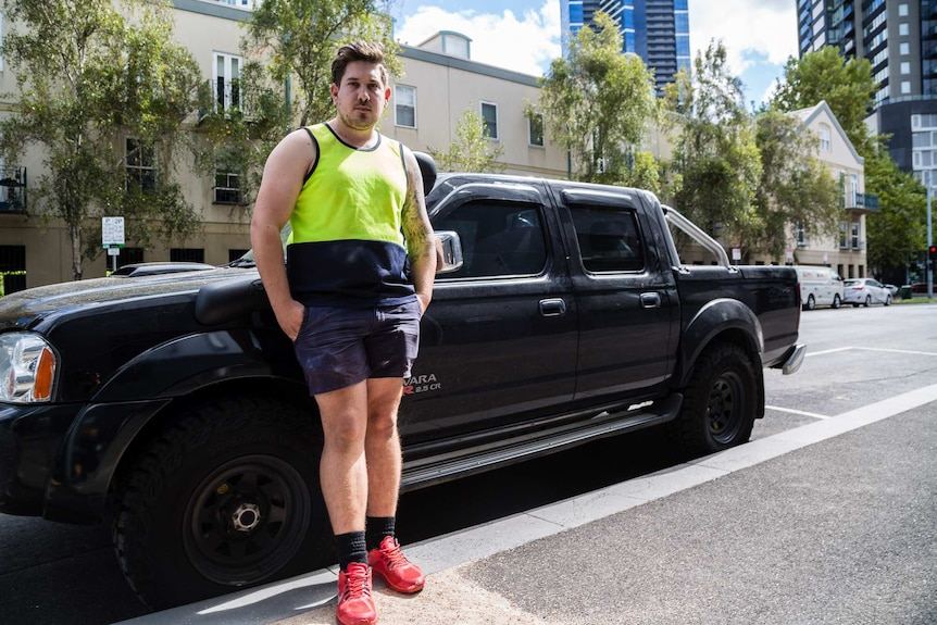 Dressed in a high-visibility singlet and shorts, Alex stands in front of a ute.