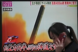 A woman walks past a TV screen broadcasting news of North Korea's missile launch