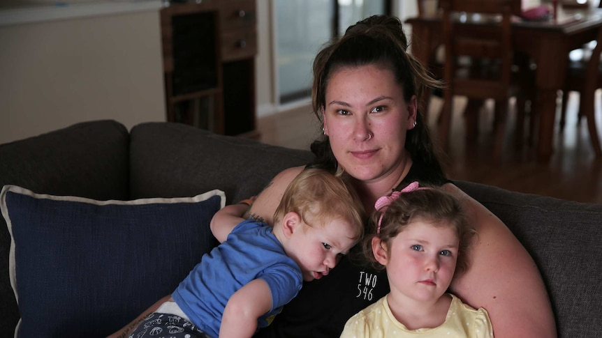 A woman sits with her children on a couch