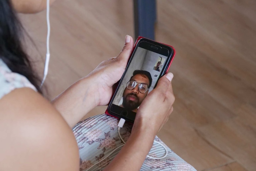 Asma Mukhi's hands hold a mobile phone during a video call, with her husband seen on the screen.
