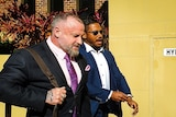 Two men in suits walk past journalists into court.