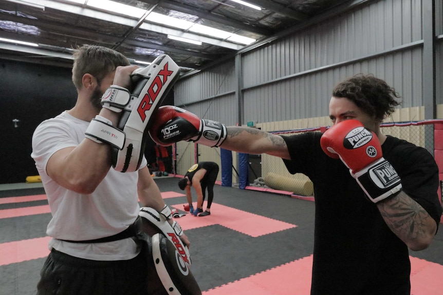 Two mixed martial arts fighters training in a gymnasium