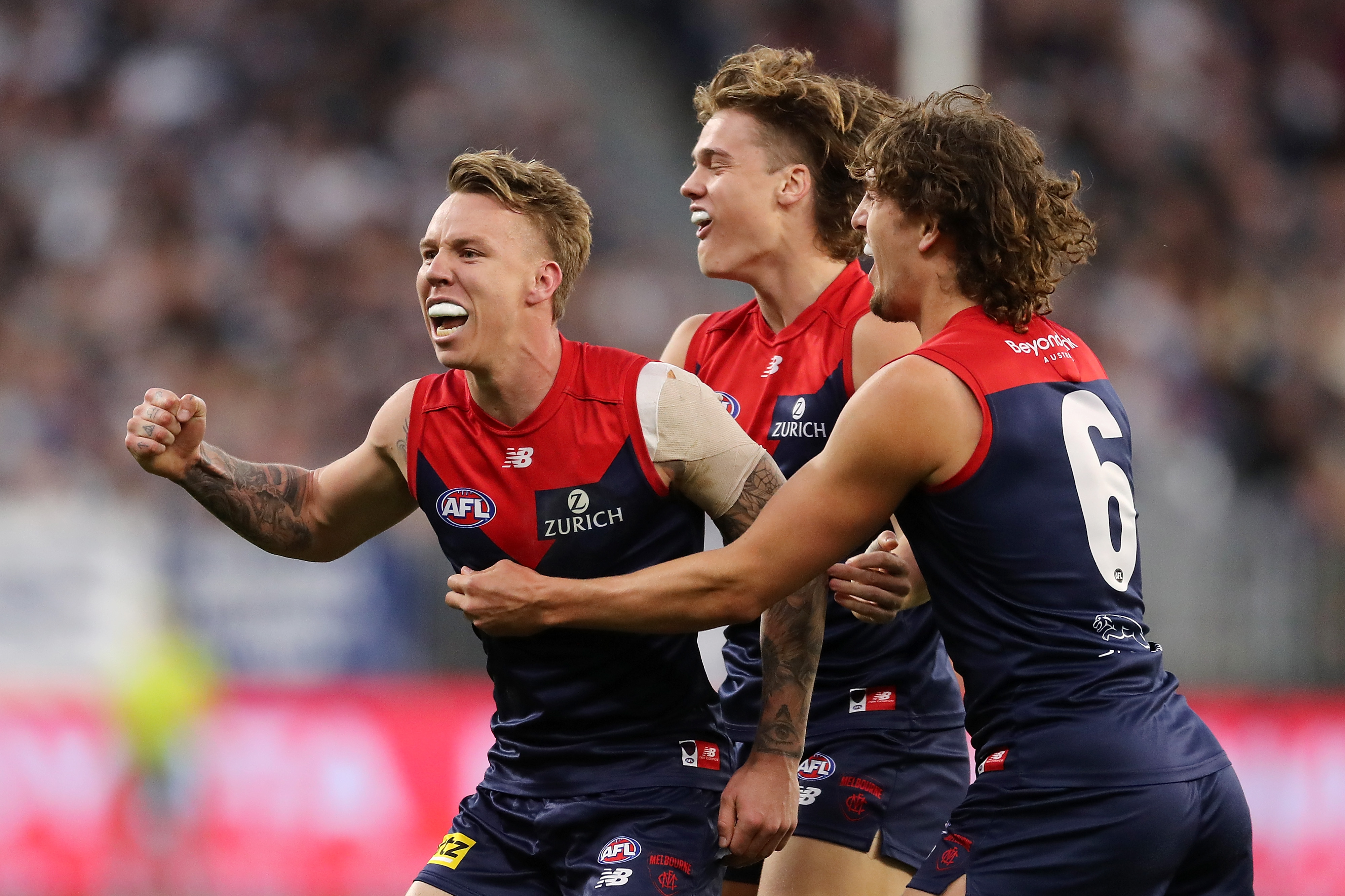 Three Melbourne AFL players embrace as they celebrate a goal.