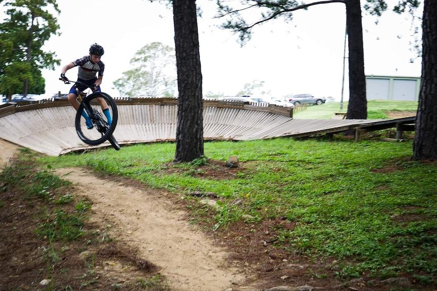 Kid launching mountain bike off jump