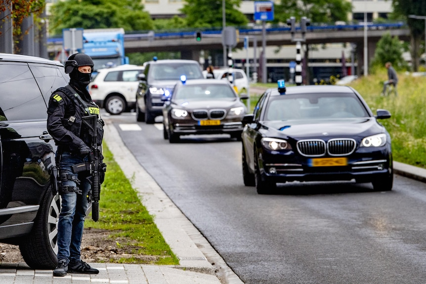 A masked police officer holding a long arm stands next to a road as cars with blues on on their roofs drive past.