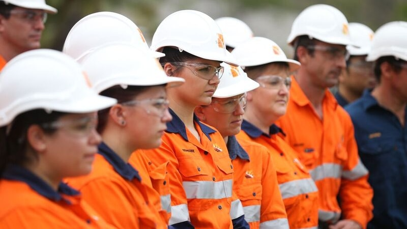 Workers wearing high vis and white hard hats gather and look to the right.