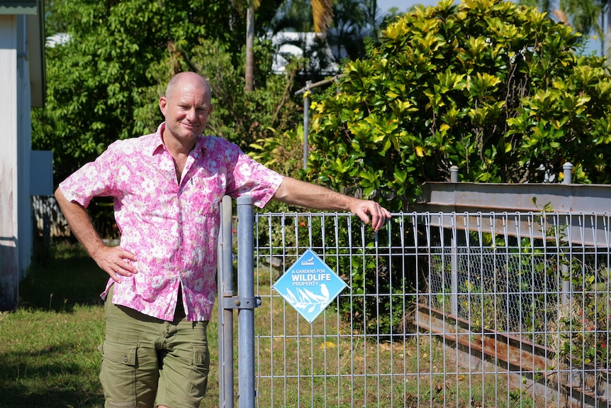 """Man in pink floral shirt leaning against a wire fence carrying a """"gardens for wildlife property"""" sign"""