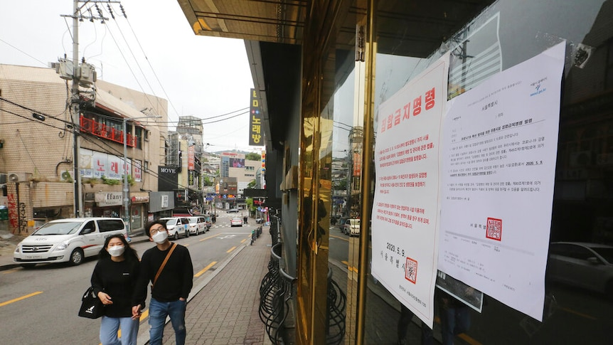 A notice on a closed dance club in Seoul says gatherings are prohibited.