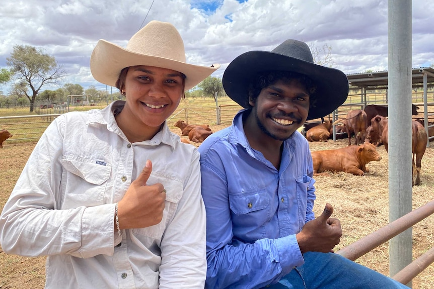 Lettoya Haji-Ali and Kendrick James sitting on the top rail of the cattle yards in front of their freshly yarded cattle.