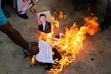 A photograph of the Chinese president is thrown into a fire.