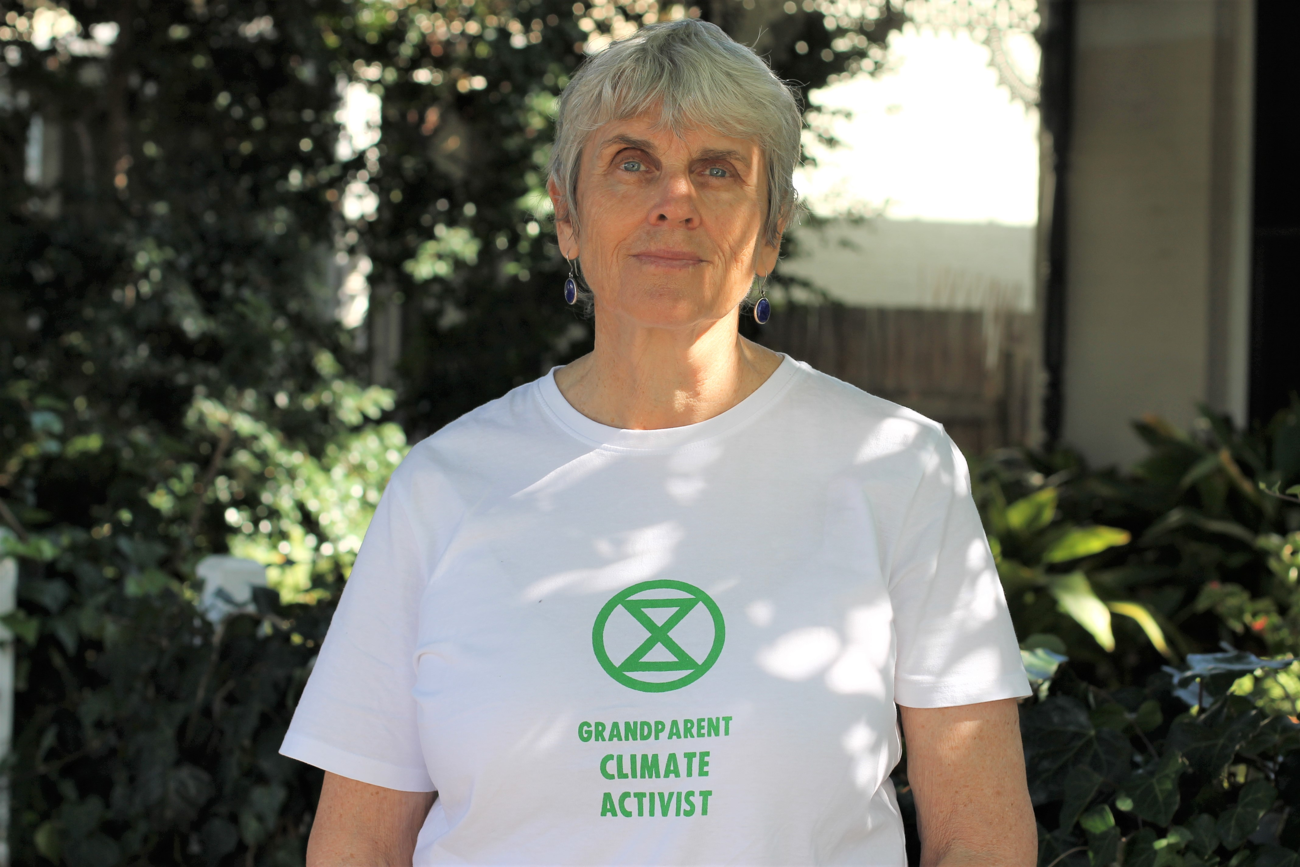"""Heath Greville standing in front of a garden with a white t-shirt on with words """"Grandparent climate activist"""""""