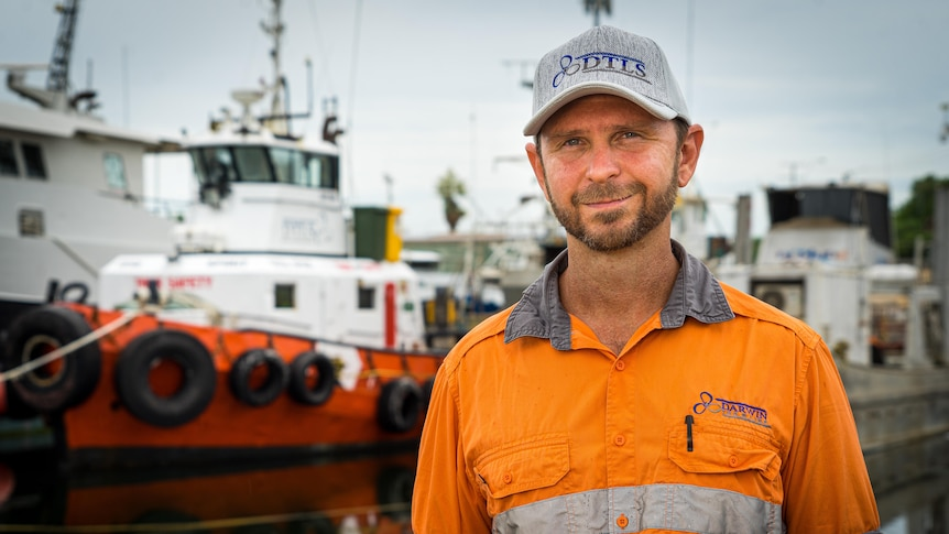 Peter West, wearing an orange overalls and a cap, looks ahead, with boats in the background.