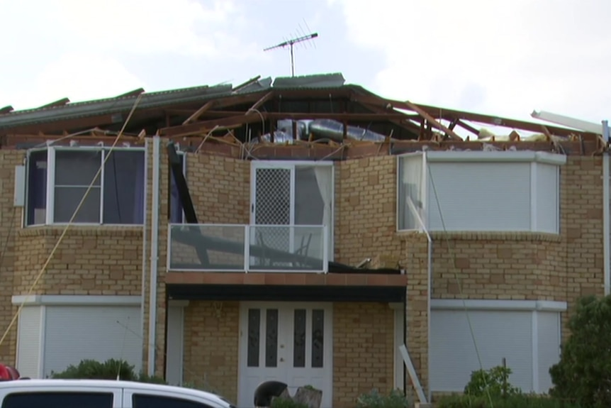 A two-storey house with a damaged roof sitsd in the foreground with grey skies overhead.