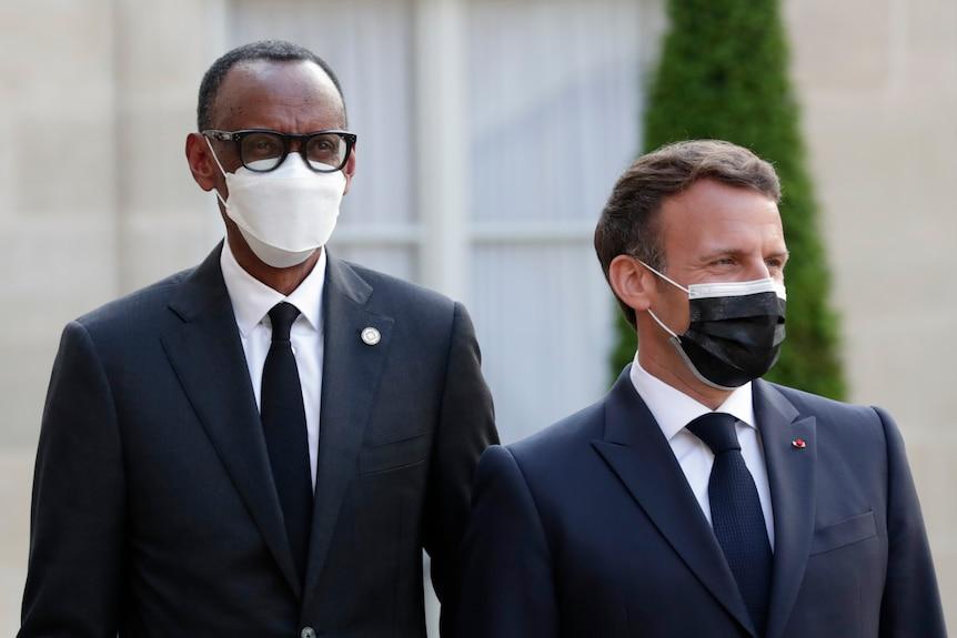 Rwanda President Paul Kagame and French counterpart Emmanuel Macron stand wearing face masks
