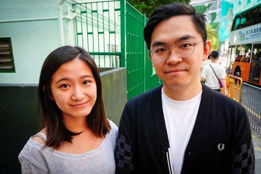 A sister and brother stand in the street in Hong Kong.