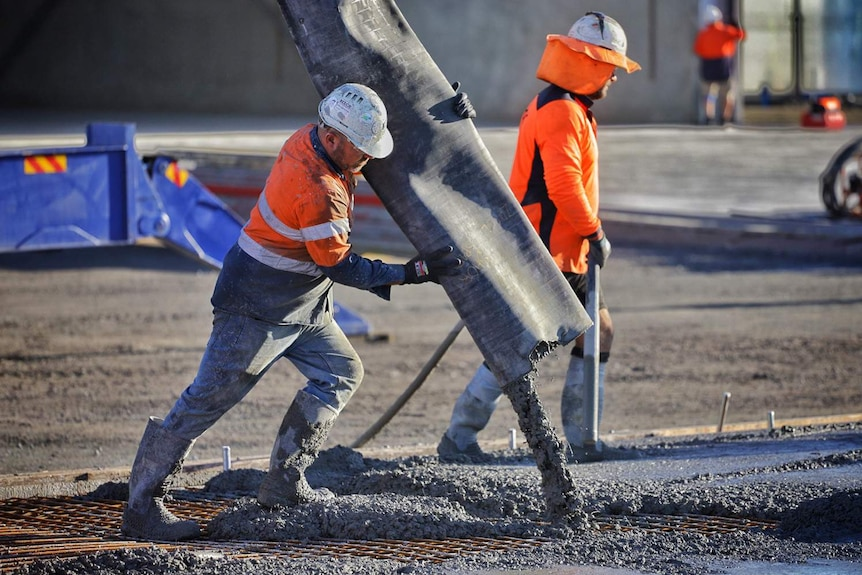 A worker pours concrete at a building construction site in Brisbane.