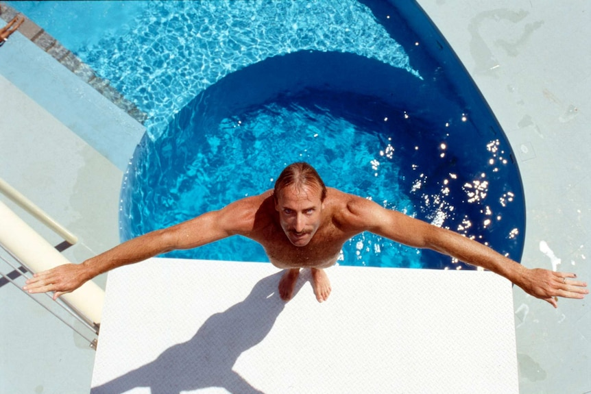 A man preparing to dive into a pool