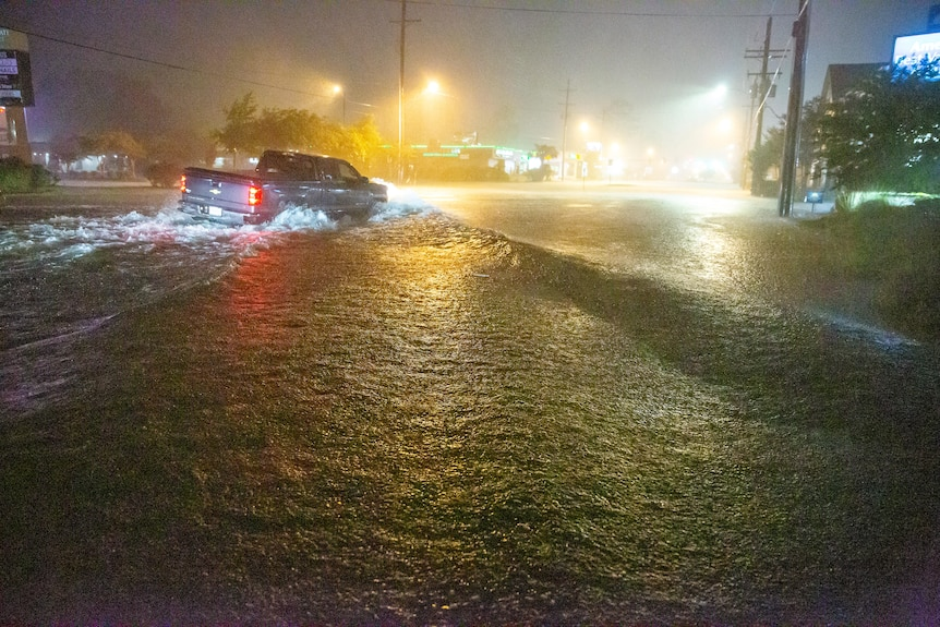 A ute navigates a flooded Gause Boulevard in Slidell, Louisiana