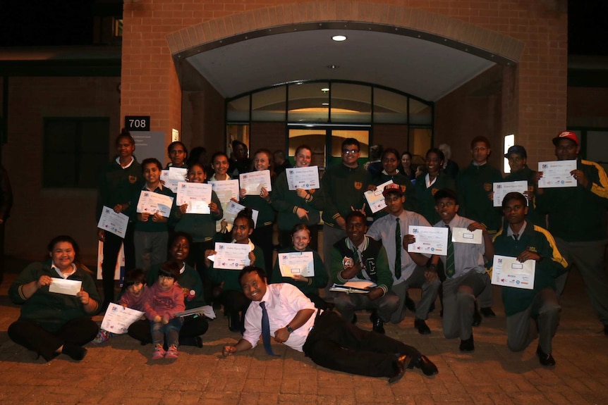 The students hold up certificates out the front of their school.