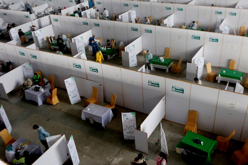 Senior citizens receive the Sinopharm coronavirus vaccine in cubicles as seen from an aerial view.