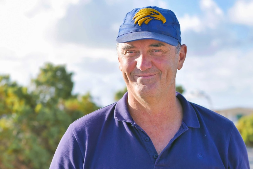 A man wearing a blue baseball cap and blue polo shirt grins as he stands outdoors.