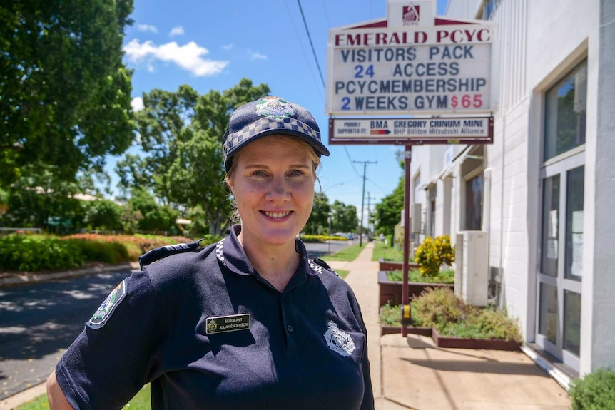 Sergeant Julia Henderson smiles outside the Emerald PCYC building in her Queensland Police Service uniform