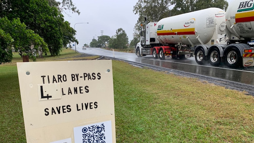 """A sign saying """"4 lanes saves lives"""" on a busy road."""