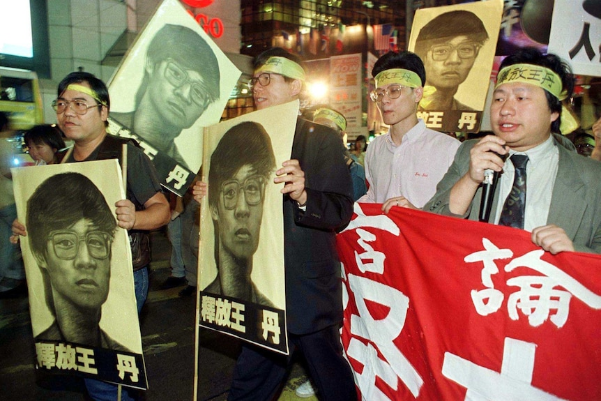 Demonstrators hold banners and portraits of detained Chinese dissident Dan Wang.