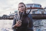 Volunteer Harriet Spark in her snorkelling gear, holding a handful of straws retrieved from the ocean.
