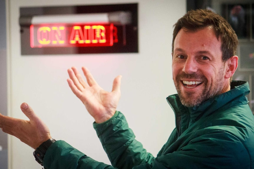 A man in radio studio with his hands raised smiling at the camera, someone who found job satisfaction after a career change.