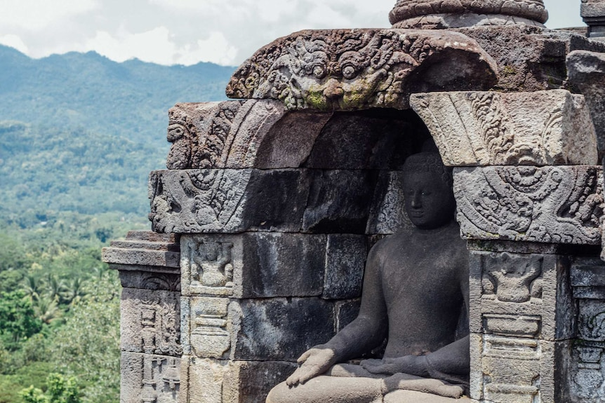You see a slightly weathered, colossal classical statue of the Buddha nestled in an alcove decorated with with dragons.