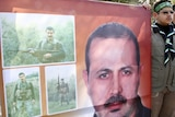 A Hamas support holds a picture of Al Mabhouh at his funeral in Syria.